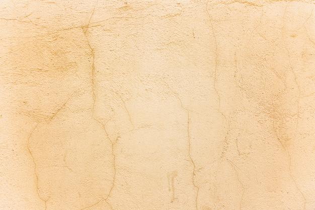 Parede de concreto bege com rachaduras. espaços e texturas. fechar-se. espaço para texto.