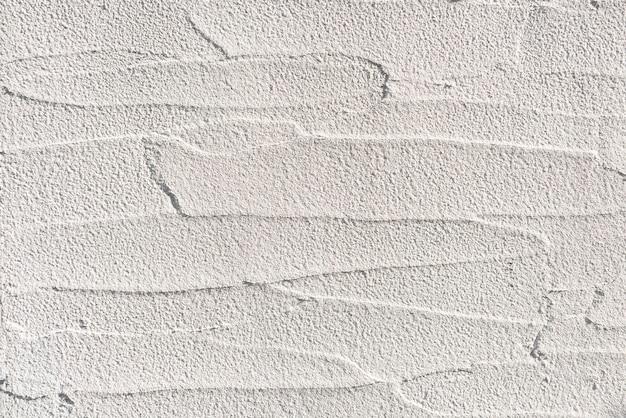 Parede de concreto branco em estilo moderno iluminada com luz suave e sua superfície em alto relevo alternada.