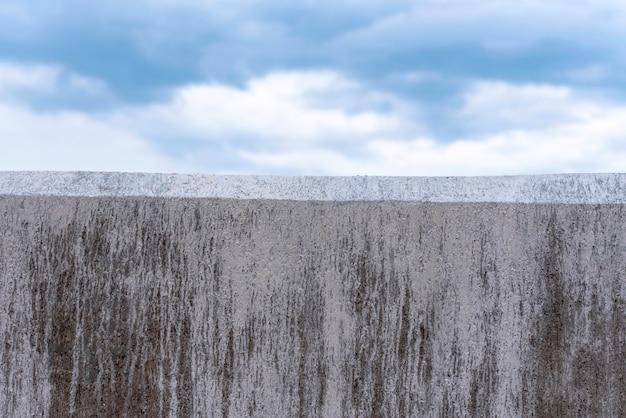 Parede de concreto cinza como fronteira e céu azul como pano de fundo