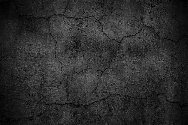 Parede de concreto preta coberta de rachaduras. superfície sombria da placa de cimento