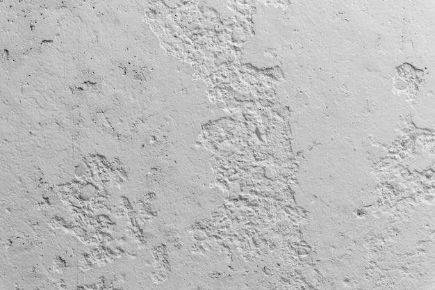 Parede de concreto preto e branco com pedaços de gesso caiu