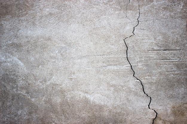 Parede de concreto rachada coberta com superfície de cimento cinza