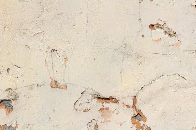 Parede de concreto rosa com arranhões e danos. fundo abstrato
