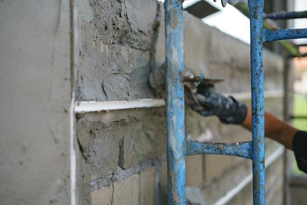 Parede de construção de trabalho de trabalhador e linha de sulco upvc com cimento de gesso