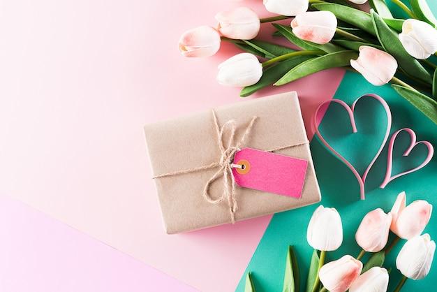 Parede de cores pastel com flores tulipa e caixa de presente com cartão