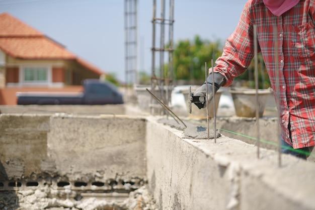 Parede de edifício de trabalho de trabalhador com cimento concreto