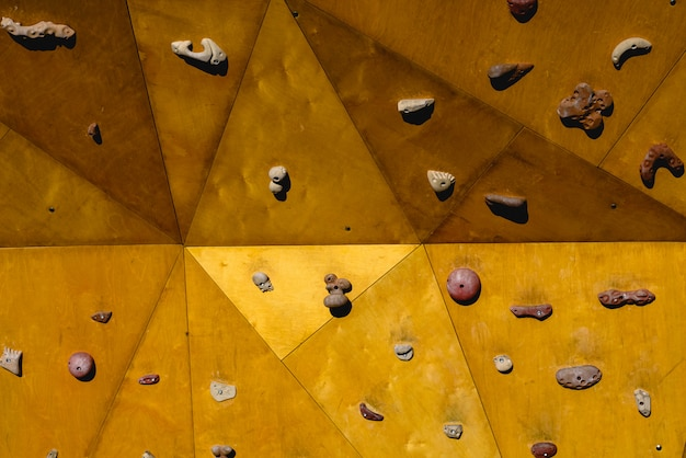 Parede de escalada amarela no sol do ar aberto.