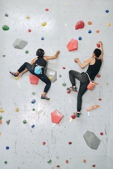 Parede de escalada de homem e mulher no ginásio