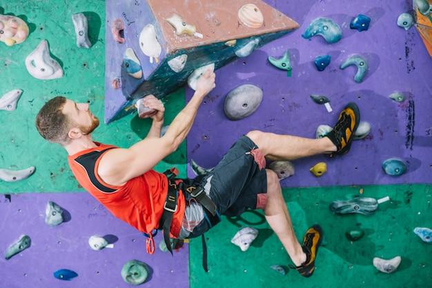 Parede de escalada desportivo homem no ginásio