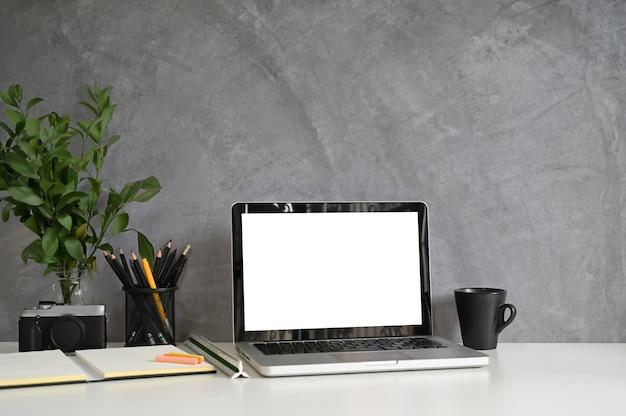 Parede de loft de espaço de trabalho e computador portátil, café, lápis, câmera na mesa