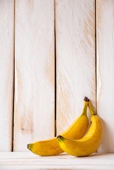 Parede de madeira branca com duas bananas amarelas.