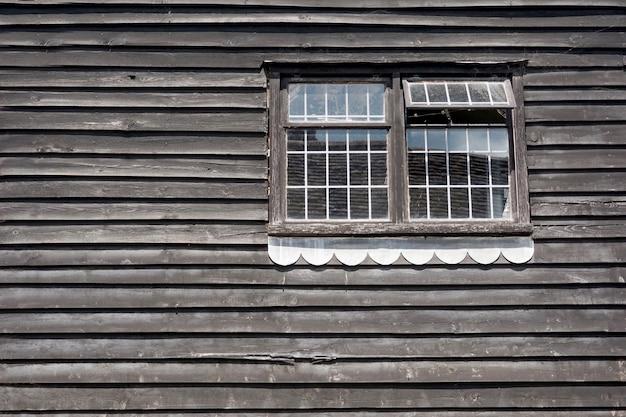 Parede de madeira e duas janelas clássicas da antiga casa
