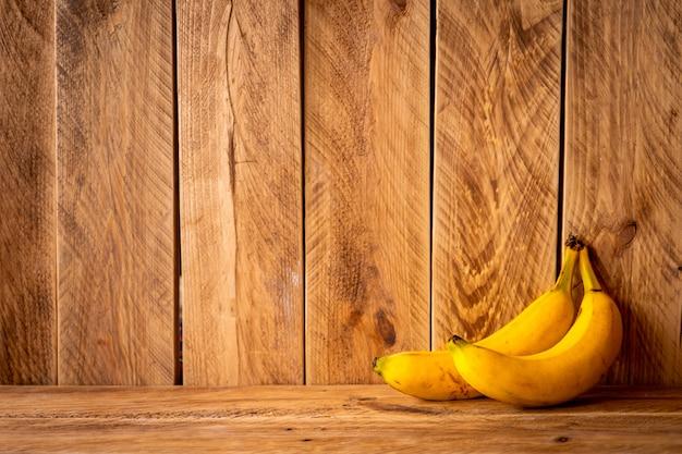 Parede de madeira marrom com duas bananas amarelas