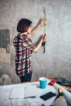 Parede de medição da mulher na cozinha