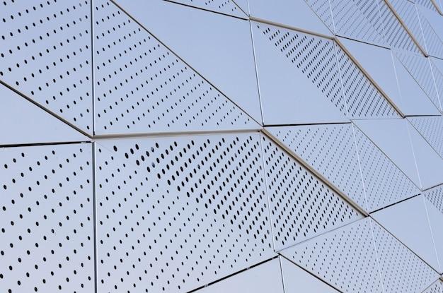 Parede de metal lisa com padrão triangular e aberturas redondas