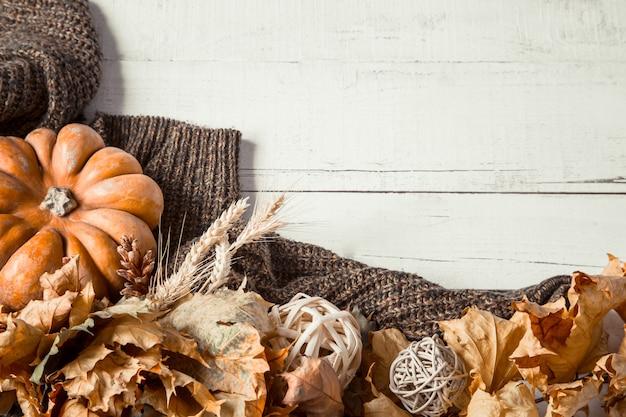 Parede de outono com artigos decorativos e abóbora.
