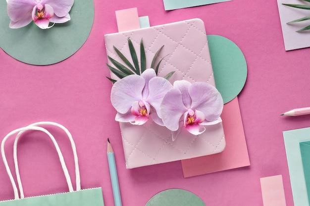 Parede de papel floral nas cores rosa e hortelã. flores da orquídea na parede geométrica com cópia-espaço.