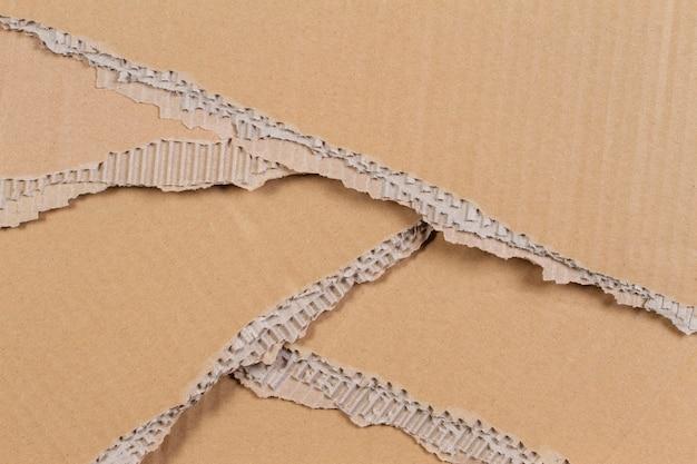 Parede de papelão bege rasgado com textura de borda irregular