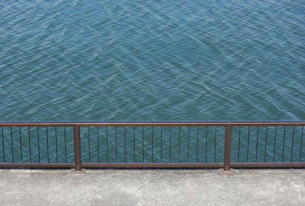 Parede de passeio com a cerca de aço do cano do punho perto do lado do rio.