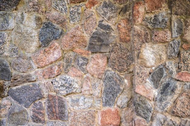 Parede de pedaços de granito de pedras fixadas com cimento