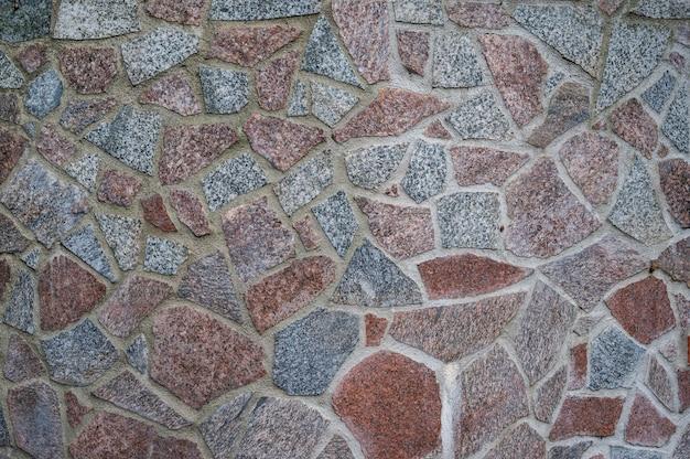 Parede de pedaços de granito vermelho e cinza de pedras fixadas com cimento
