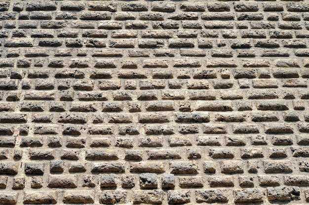 Parede de pedra antiga com fundo de tijolos planos