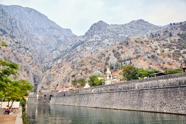 Parede de pedra da antiga fortaleza de kotor, montenegro. igreja e montanhas ao fundo