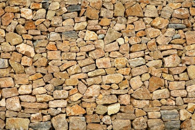 Parede de pedra de alvenaria dourada do edifício antigo