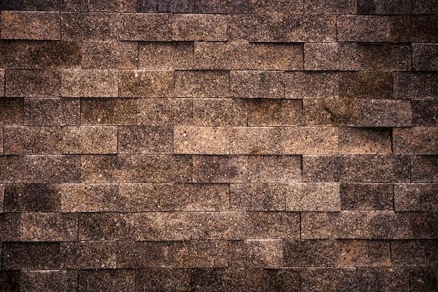 Parede de pedra de tijolos retangulares de granito marrom como pano de fundo.