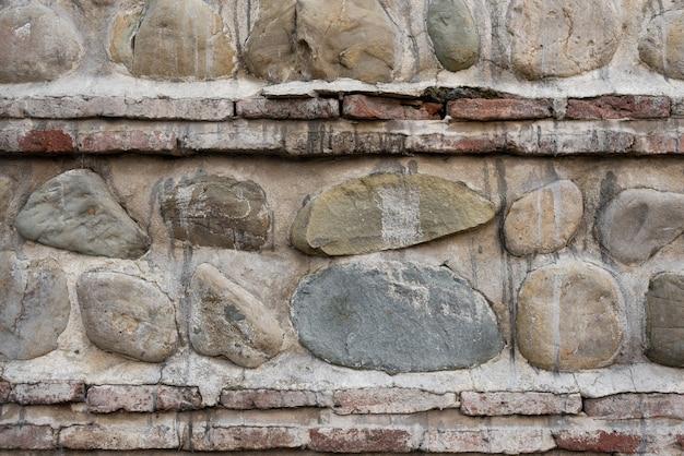 Parede de pedra. fundo. camadas verticais e horizontais de pedra