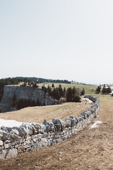 Parede de pedra perto de um penhasco em um campo verde sob um céu nublado