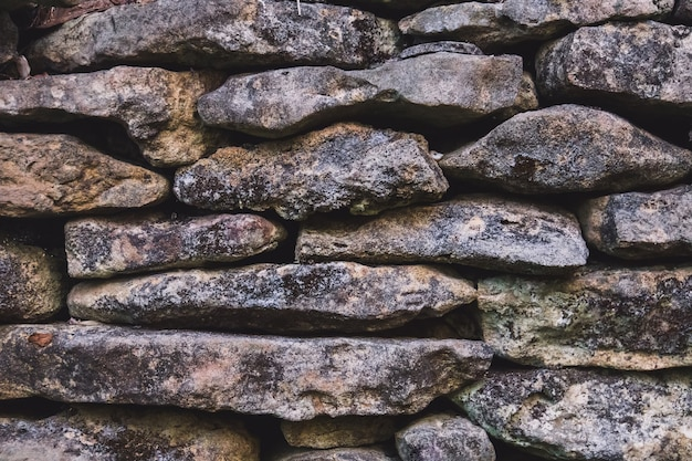 Parede de pedra velha. a textura da pedra coberta com musgo