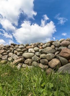 Parede de pedra velha com grama verde na frente e céu azul com nuvens acima, imagem vertical