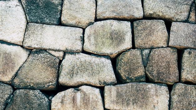Parede de pedra velha da textura do fundo do sumário do grunge