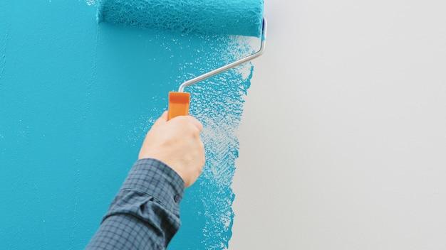 Parede de pintura de homem com tinta azul com rolo. trabalhador da construção civil, ferramenta, renovação de apartamento.