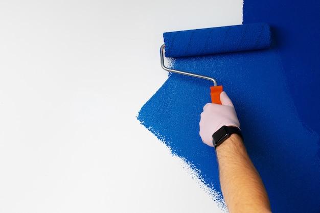 Parede de pintura de mão masculina com luvas na cor azul clássica