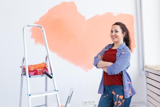 Parede de pintura de mulher adorável. conceito de renovação, redecoração e reparação.