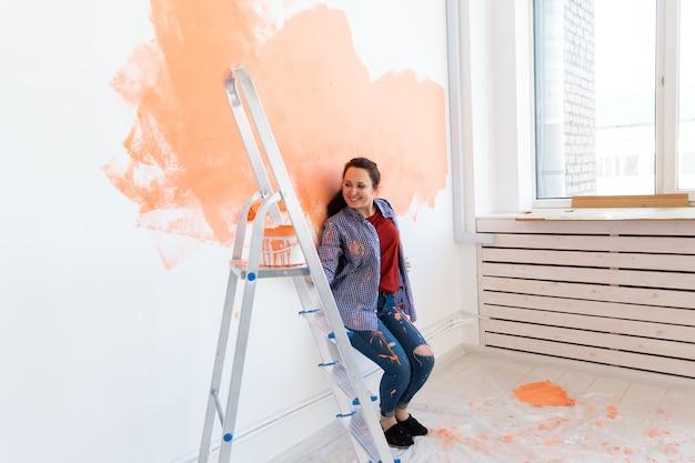 Parede de pintura de mulher adorável. conceito de renovação, redecoração e reparo.