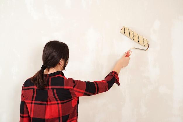 Parede de pintura de mulher jovem na sala. mulher pinta paredes com um rolo.