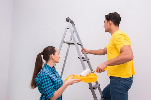 Parede de pintura jovem casal em casa