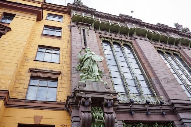 Parede de prédio antigo feito de tijolos amarelos e rosa com estátuas verdes de uma artista feminina e uma criança - são petersburgo, rússia, outubro de 2020