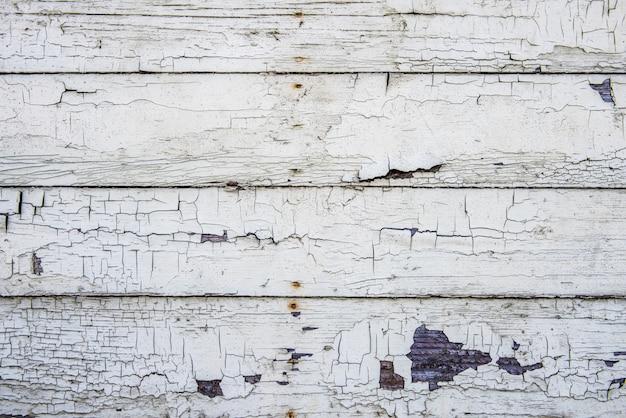 Parede de tábua de madeira com tinta branca velha rachada