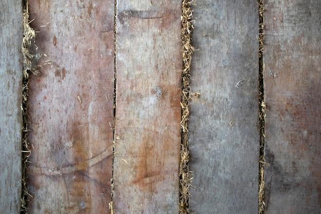 Parede de tábuas velhas, teto, textura de fundo do chão com feno na parte de trás