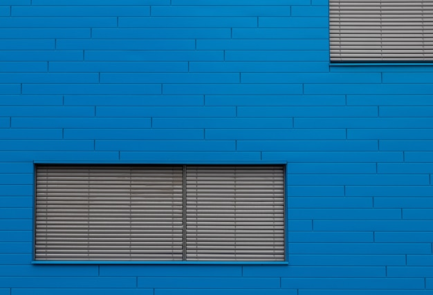 Parede de tijolo azul com persianas cinza