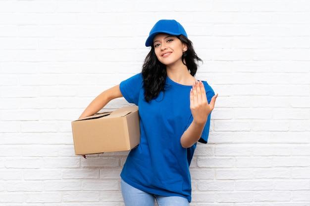 Parede de tijolo branca da mulher nova da entrega que convida para vir com mão. feliz que você veio