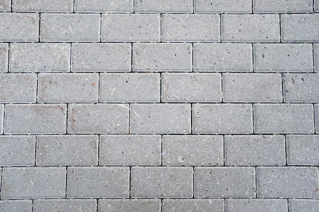 Parede de tijolo cinzenta de um novo edifício ou calçada.