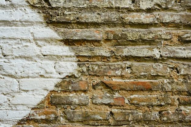 Parede de tijolo com a seta branca grande que indica o sentido, fundo com espaço da cópia.