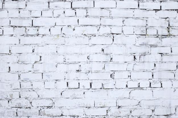Parede de tijolo envelhecida e desgastada colorida em branco. fundo de parede de tijolo branco