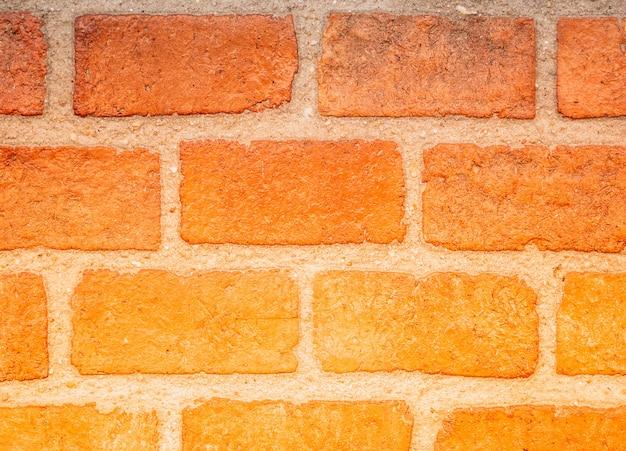 Parede de tijolo laranja degradê com creme linhas de concreto para o fundo