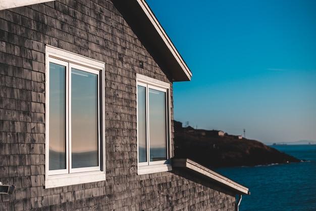 Parede de tijolo marrom perto da janela de vidro emoldurado branco